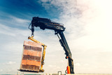 industrial crane lifting and moving brick pallet on construction site. Moving bricks with pallet - 212792471