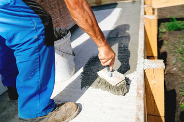 industrial worker on construction site laying sealant and primer for waterproofing cement