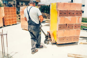 industrial mason, construction worker transporting bricks on construction site