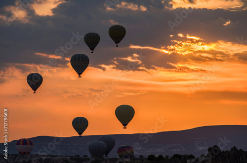 Hot air balloons take off at sunrise over Cappadocia, Goreme, Turkey.