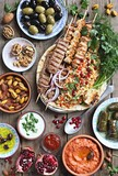 Middle eastern, arabic or mediterranean dinner table with grilled lamb kebab, chicken skewers with roasted vegetables and appetizers variety serving on wooden outdoor table. Overhead view.  - 212797284