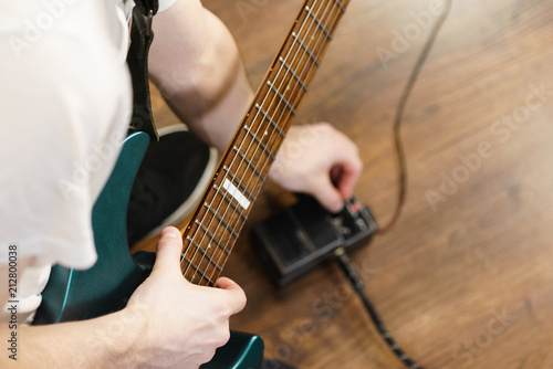 Man adjusting guitar effects pedal - 212800038