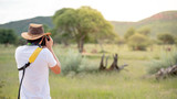 Young man traveler and photographer taking photo of wildlife animal in African safari. Wildlife photography concept - 212800643