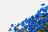 Blue Cornflower border on white wooden background. Top view, copy space. Summer background