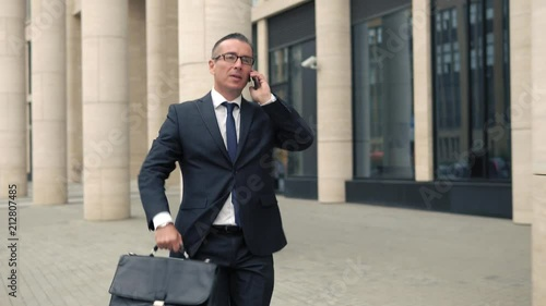 Poster Cheerful businessman walking on street and talking on the phone