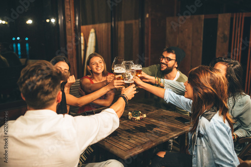 Foto Murales Group of friends drink beer on the terrace and toast during summer night
