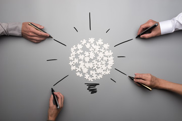 Top view of  white scattered puzzle pieces and businesspeople hands © Gajus