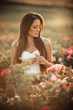 Happy smiling woman is resting in pink blossom garden of beautiful roses over sunset lights