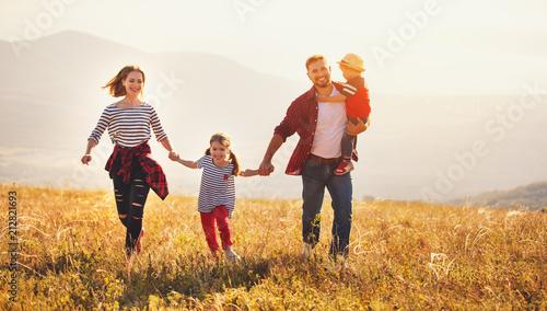 Szczęśliwa rodzina: matka, ojciec, dzieci, syn i córka na zachód słońca