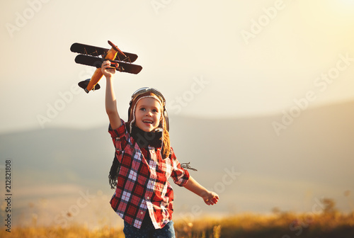 Leinwanddruck Bild Child pilot aviator with airplane dreams of traveling in summer  at sunset