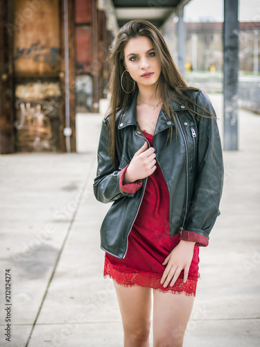 Poster Young woman in modern city setting, wearing minidress and black leather jacket