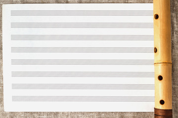 Simple wooden flute on a background of pure sheet music © Nbaturo