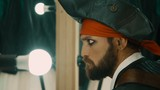 Bearded man in costume of pirate rehearsing facial expressions in front of mirror before performance or before shooting a movie - 212842480