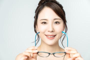 メガネを外す女性 © metamorworks