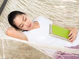 Woman sleep on hammock with tablet on the beach. - 212843437
