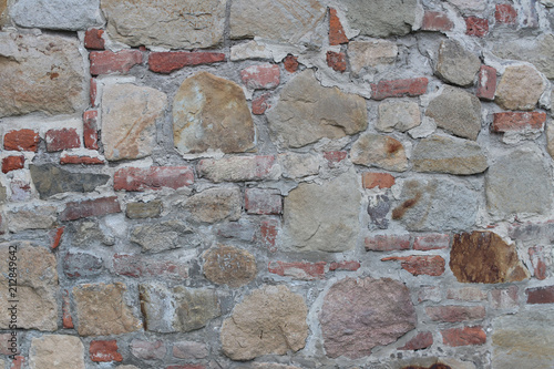 Fototapeta Ancient medieval stone masonry. Texture of a fragment of a wall of an old structure. A background for design and creative work. Decoration and exterior decoration of the building. Construction works.