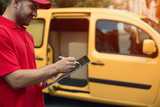 Man in red signs delivery on touchscreen tablet. Cropped shot of man wearing red shirt signing tablet for delivery. Yellow car in background. - 212854216