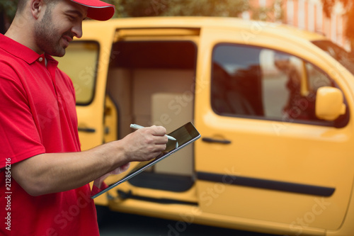 Man in red signs delivery on touchscreen tablet. Cropped shot of man wearing red shirt signing tablet for delivery. Yellow car in background. © Svyatoslav Lypynskyy
