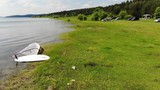 Windsurf with the sail laying on the beach of a lake with green grass and beautiful nature. - 212855258