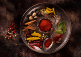 Indian spices and herbs on a plate on a dark concrete background - 212855424