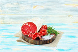 Sliced cured coppa with spices and a sprig of rosemary. - 212859615