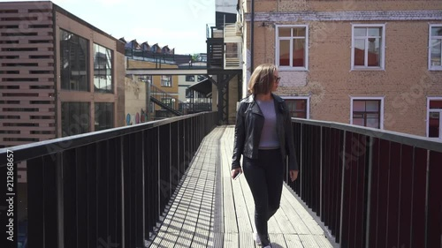 Poster Young woman with a mobile phone walking outdoors