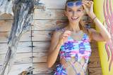 young sexy woman wearing cap, sunglasses and bathing suit marine style, standing on wooden vintage wall with reed in full sunlight - 212869861