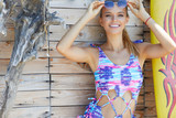 young sexy woman wearing cap, sunglasses and bathing suit marine style, standing on wooden vintage wall with reed in full sunlight - 212869869