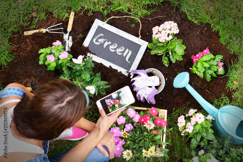 Poster Portrait of a woman (girl) taking care of the garden, she plantes flowers. Concept: farm, work, nature