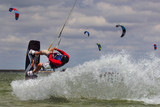 professional kiter makes the difficult trick on a beautiful background of spray - 212870018