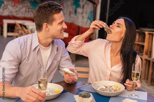 Ciesząc się ostrygami. Ciemnowłosa kobieta sobie stylowy beżowy bluzka korzystających z jedzenia ostrygi o kolację z chłopakiem