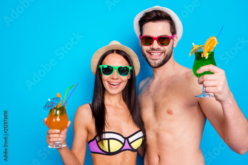Close up portrait of excited cheerful toothy smile people having with glass of summer cocktails, dressed in the swimwear, hat and eyewear. Concept of happy summer holiday and travel