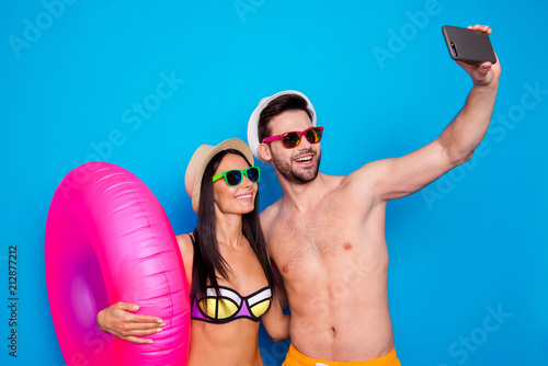 Leinwanddruck Bild Concept of summer vacation and honeymoon. A guy and a girl dressed in beachwear do selfie on smartphone with an inflatable life ring standing against a blue background