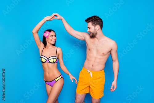 Leinwanddruck Bild Slow summer dance! Happy handsome man with yellow shorts spin charming woman in colourful swimwear and flower on here hair. Joyful happy gay turn her girlfiends waist, isolated on blue background