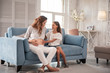 Comfortable sofa. Cute little daughter sitting on comfortable sofa near pregnant mother