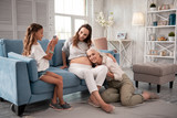 Nice photo. Cute modern girl making memorable photo of her pregnant mom with grandmother - 212879067