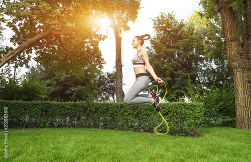 Fotobehang Fitness Young sporty woman with jumping rope