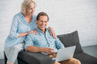 high angle view of smiling senior couple using laptop together
