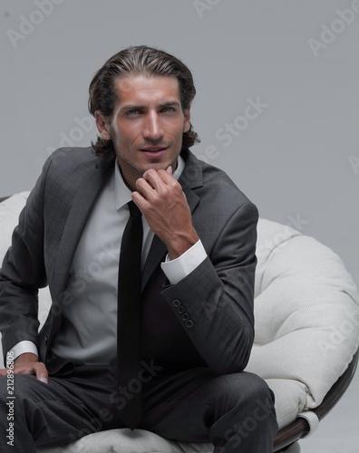 Leinwanddruck Bild confident businessman sitting in chair