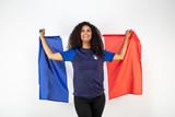 Portrait d'une jeune supportrice de l'équipe de France de football portant un chapeau , des lunettes tricolore et une écharpe de son équipe - 212905035