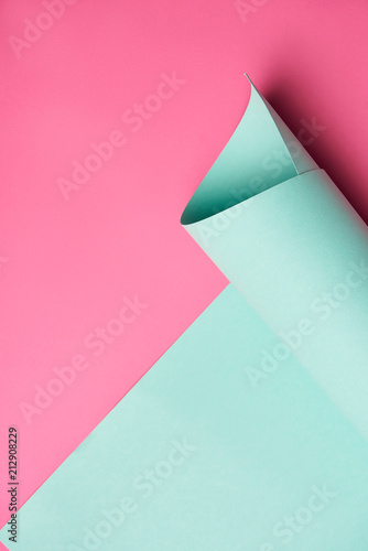 close-up view of rolled turquoise paper on creative pink background