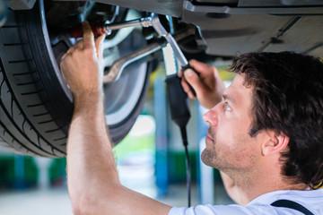 Mechanic working on car wheel in service workshop