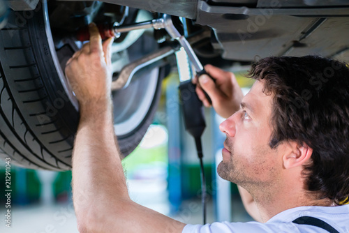 Mechanic working on car wheel in service workshop - 212911043