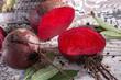 frisch geerntete und angeschnittene rote Beete und Salbeiblätter auf rustikalem Holztisch