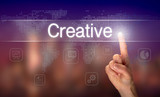 A hand selecting a Creative business concept on a clear screen with a colorful blurred background. - 212918089