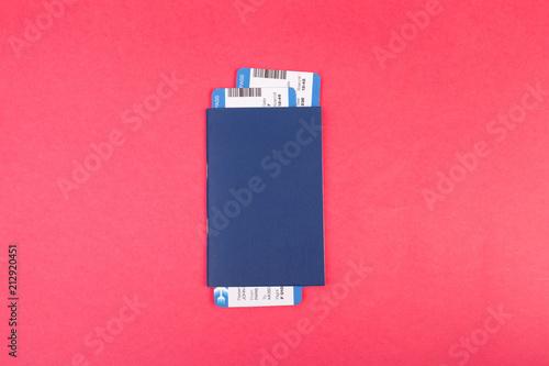 Błękitny paszport z dwa lotów biletami w nim na różowego tła odgórnym widoku