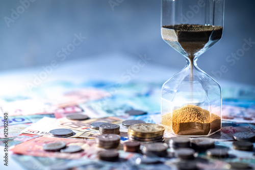 Sand running through the shape of hourglass on table with banknotes and coins of international currency. Time investment and retirement saving. Urgency countdown timer for business deadline concept - 212922450