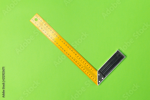 Foto Murales Construction angle ruler on green background top view