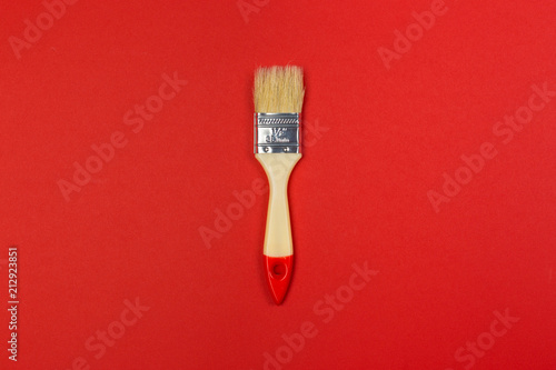 Painting brush on bright colored background top view