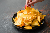 tortilla nacho chips food recipe. woman hand taking a slice of natural fried crisps of a plate - 212925261